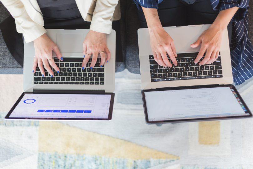 bloco-K - duas pessoas sentadas digitando em seus notebooks.