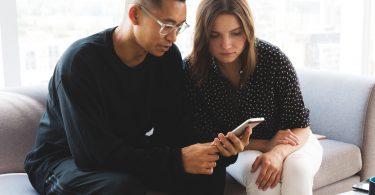 por que centralizar a manifestação do destinatário - dois colegas trabalham juntos em algo que observam no smartphone