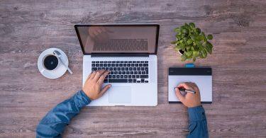 Por onde começar organizar os documentos fiscais - Homem trabalhando em seu notebook com um das mãos sobre o teclado e outra na mesa digitalizadora