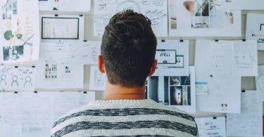 organização dos documentos fiscais - homem em pé, de costas, olhando para quadro repleto de anotações