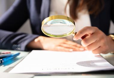 veja como diminuir erros e otimizar a conferência do SPED - mulher com uma lupa na mão investigando um documento