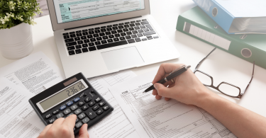 tributação NCM - homem utilizando uma calculadora enquanto preenche vários documentos expostos em cima de uma mesa com um notebook. Title content: Entenda como funciona a tributação NCM
