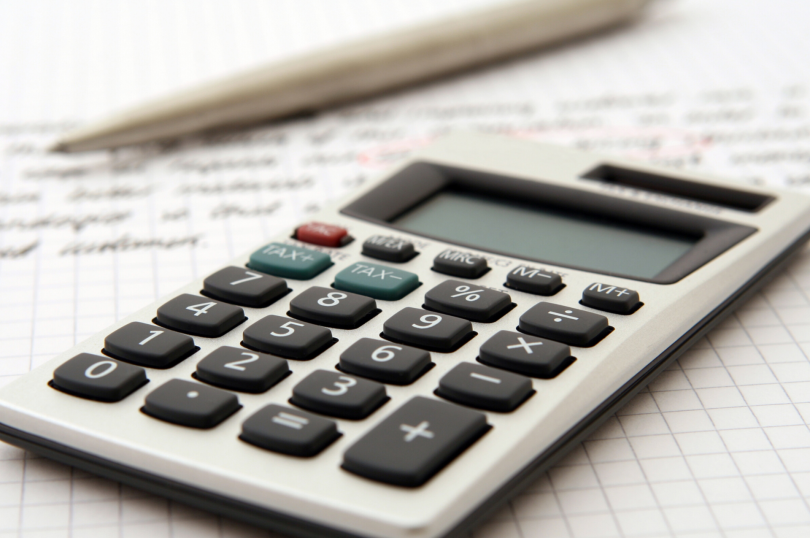 sistema tributário brasileiro - na imagem temos uma calculadora sobre uma folha de relatório com uma caneta ao fundo