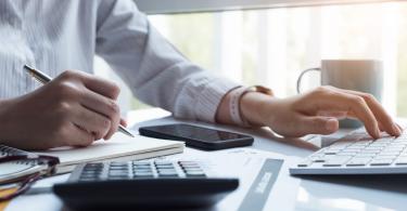 Entenda a importância do faturista - profissional trabalhando utilizando computador, calculadora e planilhas de anotação.