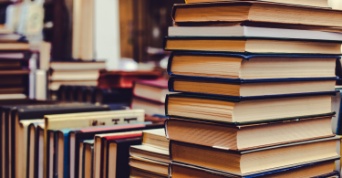 Glossário fiscal: Conheça as principais siglas utilizadas no dia a dia das empresas - Vários livros empilhados