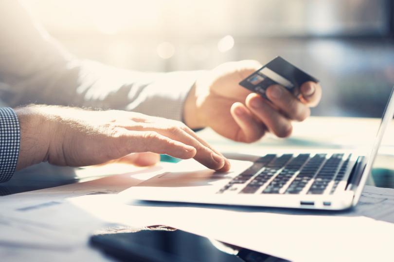 Modalidades de pagamento do ICMS-RO - Homem segurando um cartão de crédito realizando um pagamento através do seu notebook