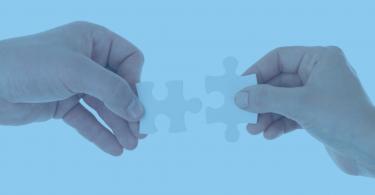 - Duas mãos segurando peças de um quebra-cabeça que se encaixam.