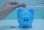 Regime Normal - Pessoa colocando moeda dentro de um cofre azul no formato de um porquinho.