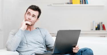 Saiba porque você não pode cadastrar produtos diferentes com a mesma NCM - Homem sentado com um computador no colo com expressão de dúvida