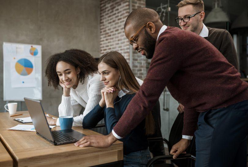 Mudanças na CST para 2022 - Mulher mostrando algo aos colegas durante uma reunião-