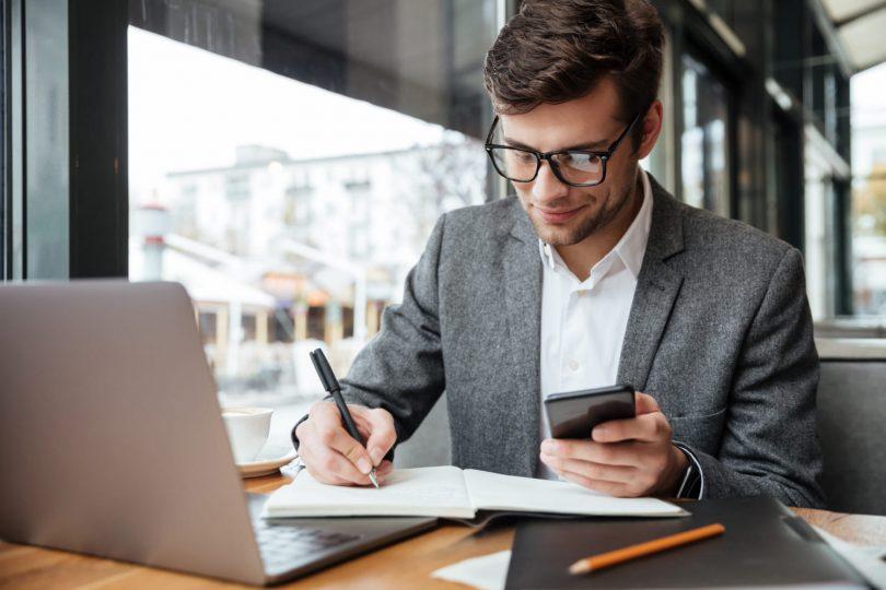 Mudanças na tabela CFOP para 2022 - Empresário sorridente em óculos, sentado junto à mesa no café com o computador portátil enquanto estiver usando o smartphone e escrevendo algo