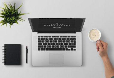 4 razões para automatizar a gestão fiscal e tributária do seu negócio - Mesa com notebook, caderno de anotações e um braço segurando uma xícara de café