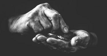 O que é fundo de combate à pobreza - Imagem preto e branco com as mãos de uma pessoa contando moedas